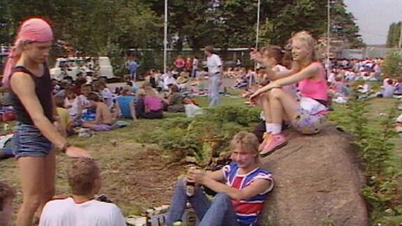 Publikum vor dem Konzert auf einer Wiese: Ein Mädchen in kurzen Hosen sitzt auf einem großen Stein, unter ihr auf dem Rasen sitzt ein Jugendlicher mit Bierflaschen