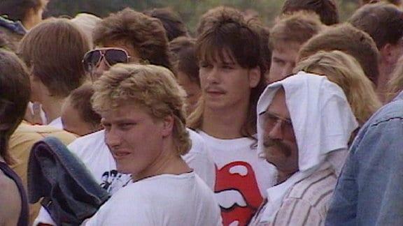 Junge Männer in Nahaufnahme, einer schnauzbärtiger hat sich ein weißes Tuch als Sonnenschutz auf den Kopf gelegt