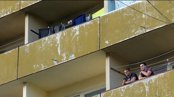 Nachaufnahme Plattenbau - zwei junge Männer auf einem Balkon.