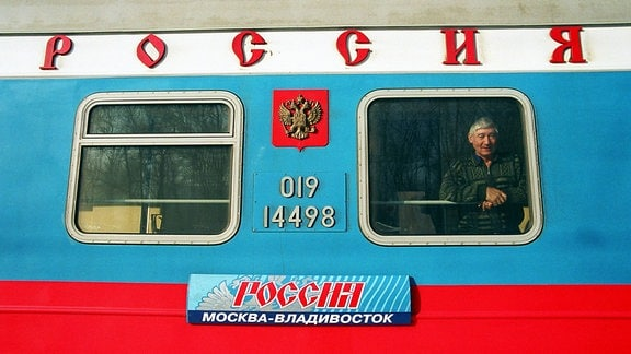 Ein Reisender am Fenster eines Waggons der Transsibirischen Eisenbahn