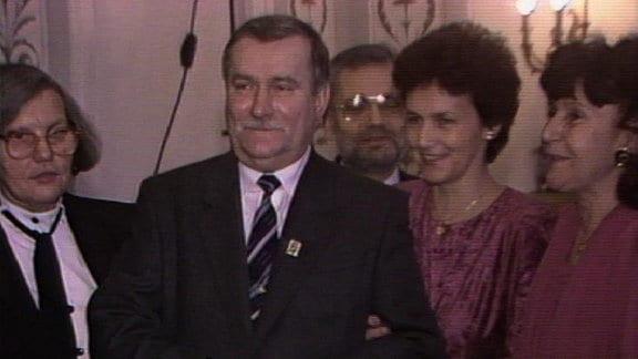 Lech Valesa lachend vor einer Gruppe Frauen.