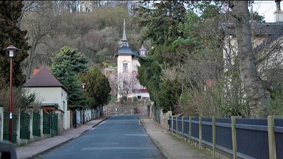 Blick auf eine Straße, an deren Ende ein Haus mit einem Turm steht.