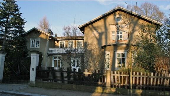 Ein älteres Haus mit zwei Haupthäusern und einem Zwischenteil, der beide Seiten verbindet.