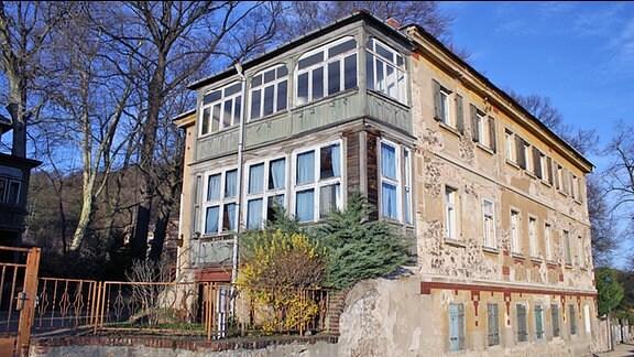 Ein sehr altes und unsaniertes Haus, das an einer kleinen Straße steht.