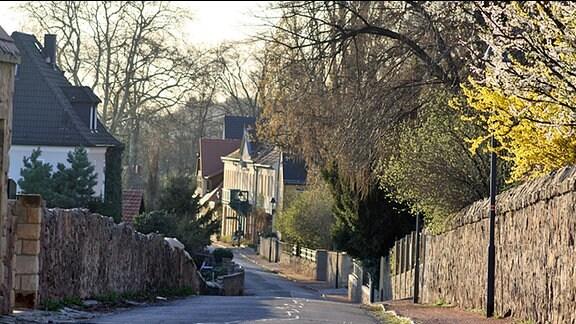 Eine romanische Straße, die abwärts führt. Links und rechts befinden sich Häuser und Steinbruchmauern.
