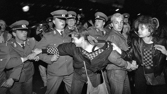 Eine Frau versucht, eine Demonstrantin von der Polizeikette weg zu ziehen. Am 7. Oktober 1989 kam es wie in anderen ostdeutschen Städten auch in Ostberlin zu Demonstrationen gegen die Machthaber in der DDR. Am Rande der offiziellen Feierlichkeiten zum 40. Jahrestag der Republikgründung bildete sich auf dem Alexanderplatz ein Protestzug mit rund 1000 meist jugendlichen Teilnehmern, der zu dem von Sicherheitskräften abgesperrten Palast der Republik marschierte. Im Verlauf der Demonstration gingen Volkspolizei und zivile Beamte der Staatssicherheit zum Teil massiv gegen Demonstranten und Journalisten vor.