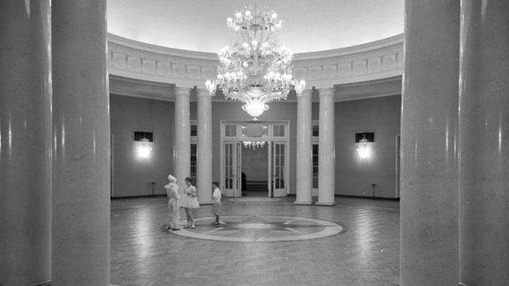 Drei Personen in einer großen, runden Halle
