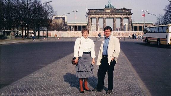 Ein Mann und eine Frau stehen 1985 vor dem Brandenburger Tor in Westberlin