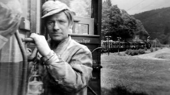 Bergmann auf dem Trittbrett seines Schichtzuges. In der Hand hält er seine Grubenlampe.