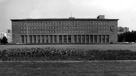 An der Fassade des Zentralkomitees der Sozialistischen Einheitspartei Deutschlands in Berlin-Mitte ist das Partei-Emblem mit dem Händedruck vor der roten Fahne zu sehen