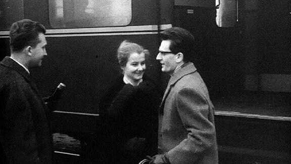 Schwarzweißbild zeigt jungen, bebrillten Mann und eine junge Frau vor einem Zug. Ein Reporter streckt dem Paar von links ein Mikrofon entgegen.