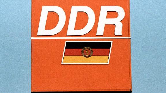 DDR-Schriftzug und Fahne auf orangefarbenem Grund