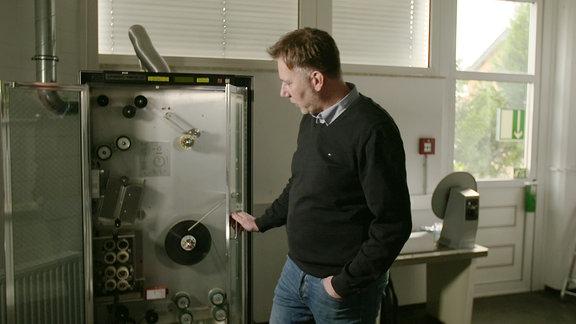 Ralf Jesse vor geöffneter Tür der Waschmaschine / sieht hinein