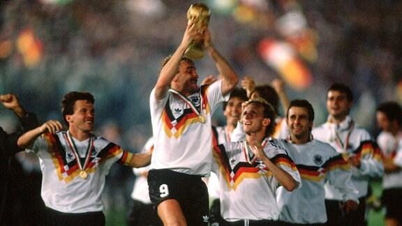Rudi Völler (vorn) präsentiert während der Ehrenrunde den FIFA Weltpokal, daneben Lothar Matthäus (li.) und Andreas Brehme