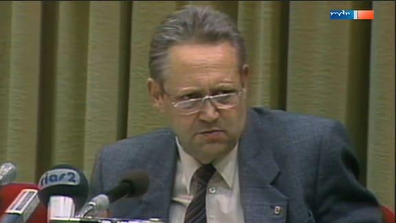 Günter Schabowski sitzt vor mehreren Mikrofonen
