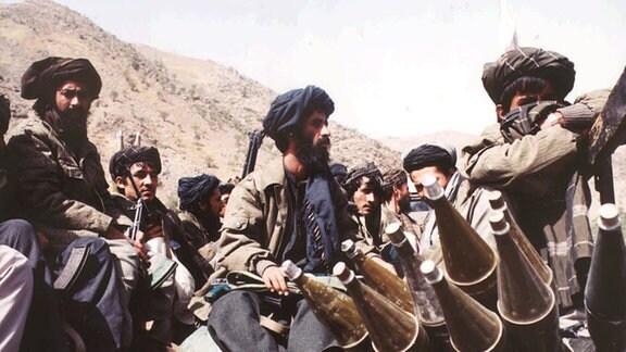 Bewaffnete Taliban-Kämpfer sitzen in einer steinigen Gebirgslandschaft.