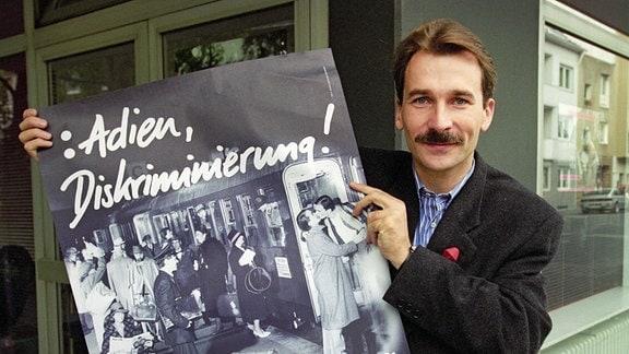 Der Kölner Volker Beck, hier am 30.08.1994 in Köln mit einem Wahlplakat, bewirbt sich auf der Liste von Bündnis 90/Die Grünen um ein Bundestagsmandat.