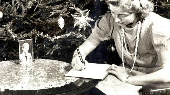 Eine Frau schreibt einen Brief vor einem Weihnachtsbaum