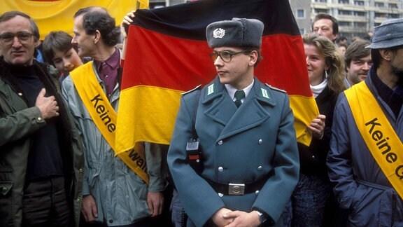 Volkspolizist vor BRD-Fahne während einer Demonstration zum Besuch von Helmut Kohl in Leipzig