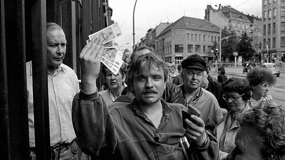 Tag der Währungsunion Deutschland, Berlin, 01.07.1990, Mann mit D-Mark und DDR Ausweis.