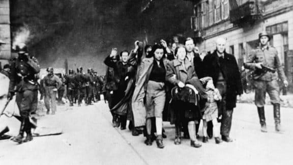Menschen werden mit erhobenen Händen 1942 von bewaffneten Soldaten duch das Warschauer Ghetto getrieben