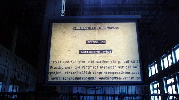 In einer Halle wird auf eine Leinwand ein Text projiziert.