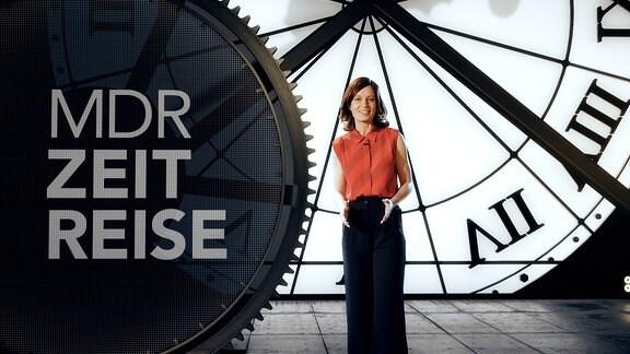 Moderatorin Janett Eger im Zeitreise-Studio vor einer großen Uhr